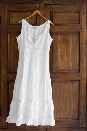 White cotton dress on wooden hanger on antique wardrobe photo
