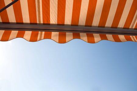 Sunshade over bright sunny blue sky
