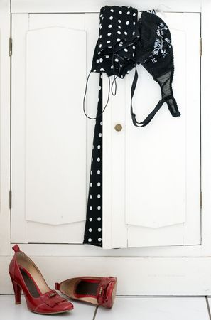 polka dot dress, black bra and red high heel shoes on white cabinet photo