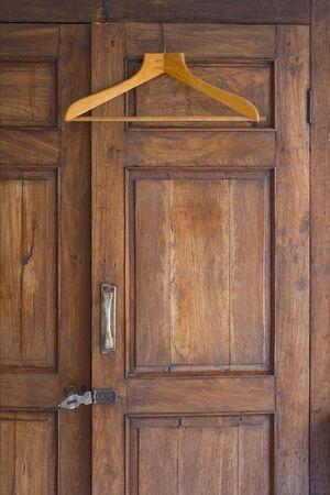 Wooden hanger on door of antique closet