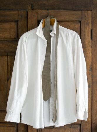 Mans shirt and tie hanging on antique closet