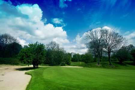 18th: 18th hole with bunker at the left side under beautifull blue sky with white clouds Stock Photo