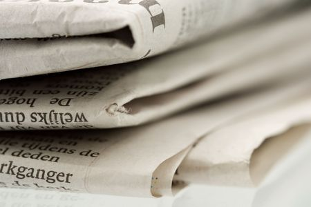 Folded newspaper on shiny reflecting surface - Close-up shot focus on foreground