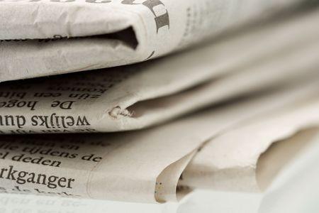 Folded newspaper on shiny reflecting surface - Close-up shot focus on foreground