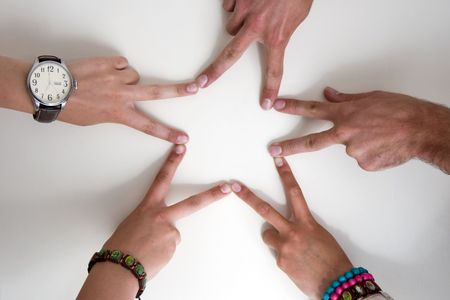 Five teenagers hands form a star. Two boy hands and three girl hands. Girls are wearing watch and bracelets