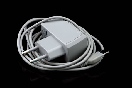 Gray cell phone charger on shiny black surface