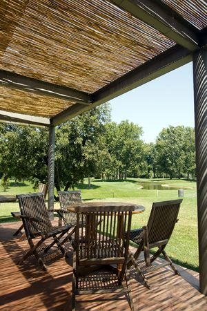 Terrace with wooden table and chairs under shelter of straw. Looking over golf course Stock Photo