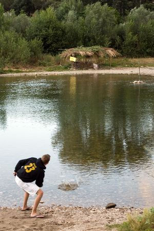 Boy skipping rock in the river