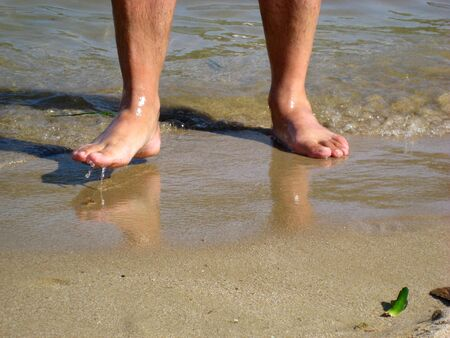 Wet men's feet in the sea on the beach Stock Photo - 3443101