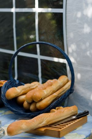 French baguettes in a blue basket. One on a cutting board. photo