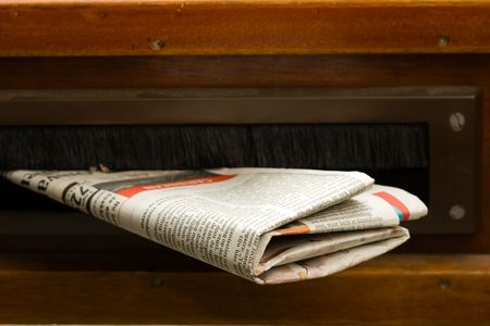 Very high resolution shot of newspaper coming in the mail box in a wooden door.