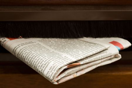 Very high resolution close-up shot of newspaper coming in the mail box in a wooden door. Stock Photo - 3480087