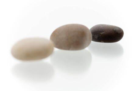 Very high resolution image.Three different colored pebbles in a row. On a white surface with reflection. High key shot with shallow depth of field. Focus on last pebble. Stock Photo - 3480074