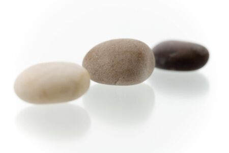 Very high resolution image.Three different colored pebbles in a row. On a white surface with reflection. High key shot with shallow depth of field. Focus on middle pebble. Stock Photo - 3480077