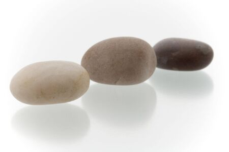 Very high resolution image.Three different colored pebbles in a row. On a white surface with reflection. High key shot with shallow depth of field.  Stock Photo - 3480079
