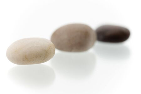 Very high resolution image.Three different colored pebbles in a row. On a white surface with reflection. High key shot with shallow depth of field. Focus on first pebble. Stock Photo - 3480078