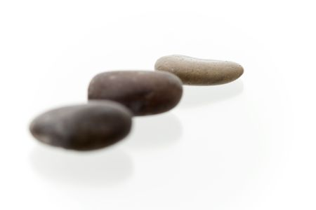 Very high resolution image. Three dark pebbles in a row. On a white surface with reflection. High key shot with shallow depth of field. Focus on last pebble. Stock Photo - 3480076
