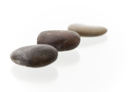 Very high resolution image. Three dark pebbles in a row. On a white surface with reflection. High key shot with shallow depth of field. Focus on middle pebble. Stock Photo - 3480073