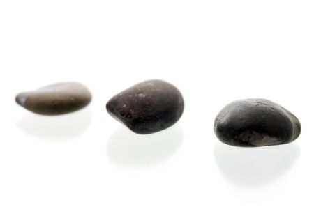 Three dark pebbles in a row. On a white surface with reflection. High key shot with shallow depth of field. Stock Photo - 3480068