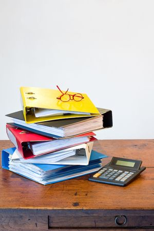Pile of colored ring binders, glasses and calculator on wooden desk photo