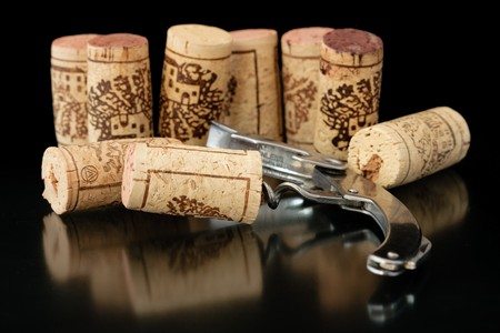 Corkscrew with corks on background