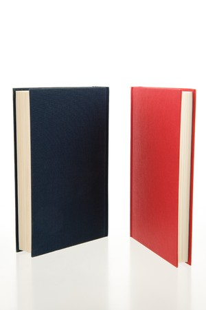 closed red and blue books standing on a reflecting white background photo