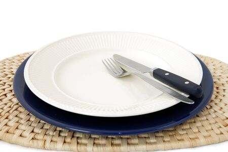 Empty off white plate on blue underplate on raffia placemat with knife and fork Stock Photo