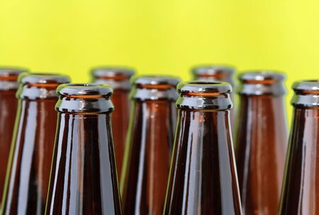 Empty beer bottles in diagonal rows in front of a bright green background photo