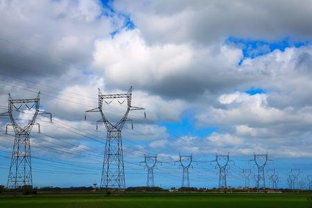 hoogspanningsmasten: Veld vol pylonen onder blauwe lucht met weinig bewolking