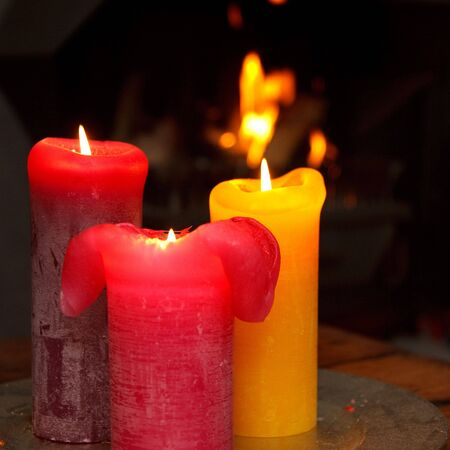 Set of three burning candles in front of a burning fire place Stock Photo - 4864318
