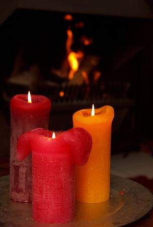 Set of three burning candles in front of a burning fire place Stock Photo