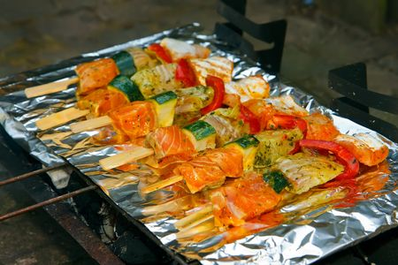 delicious fish on sticks being grilled on a foil wrapped barbecue