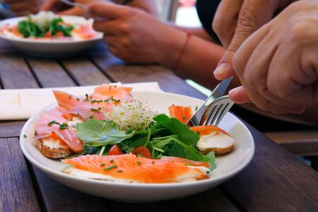 Mens hands eating a delicious salmon salad on a wooden desk photo