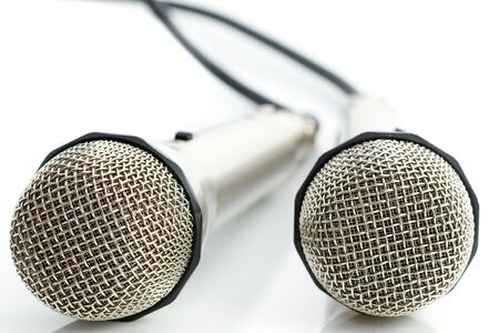 Two microphones on reflecting white background