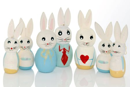 wooden easter bunnies in a row on a white reflecting background photo