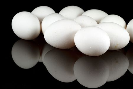 White chicken eggs on reflecting black background Stock Photo