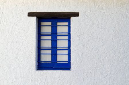 Blue painted window frame in white structured wall photo