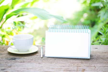 Notebook  and coffee on wooden table