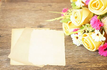 Paper sheets and invent flowers on wooden table Stock Photo