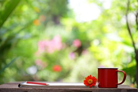 Red mug with red flower and notebooks on wooden table Stock Photo