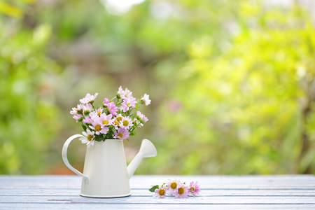 Flowers in vintage water can on wooden table