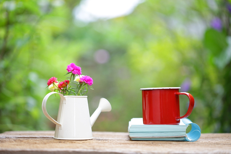 Red mug with flower and notebooks on wooden table