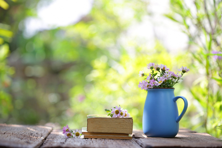 flower in blue pot and notebooks