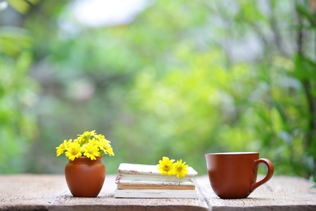 Notebook with yellow flower and cup on wooden table