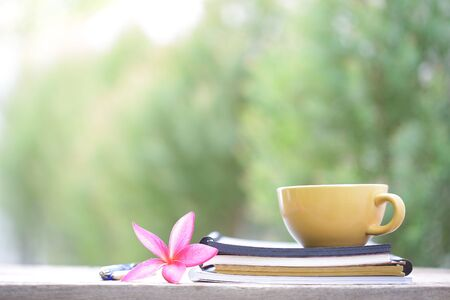 yellow coffee cup with flower and notebook on wooden table