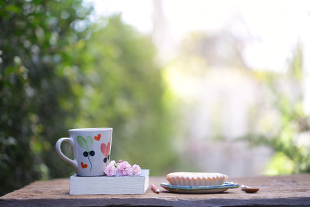 White mug with heart pattern and pie with pink fairy rose 스톡 콘텐츠