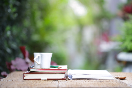 White heart shape cup and notebook at outdoor