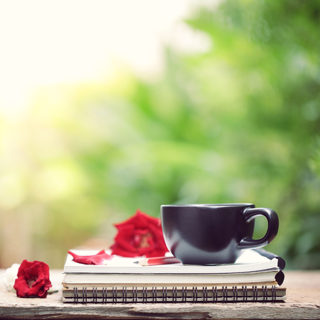 Black cup with red rose and notebook diary on wooden table