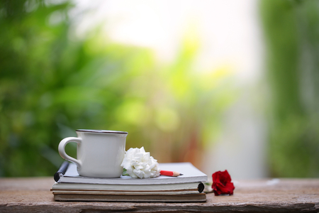 White cup and notebook with white rose