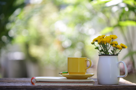 Yellow ceramic cup with flower jar and notebooks at on wooden table
